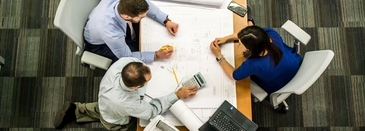 Three people sitting at a table looking over blueprints