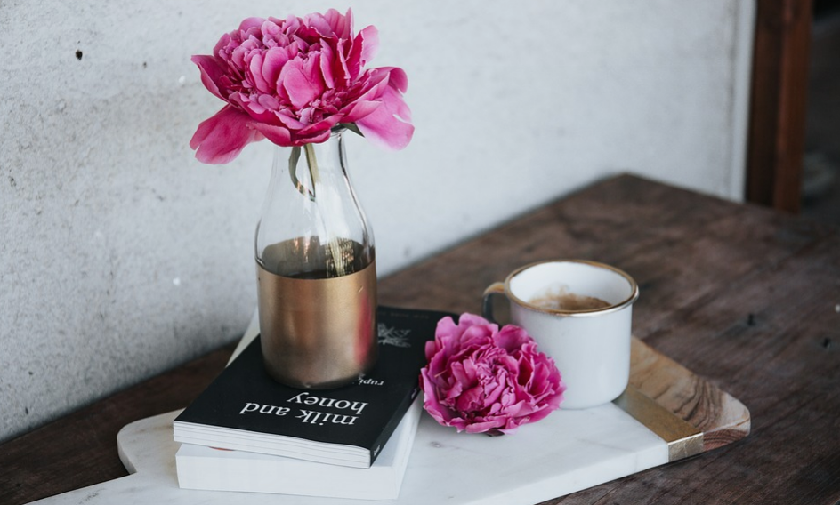 Pink peonies on a book, on a wooden table