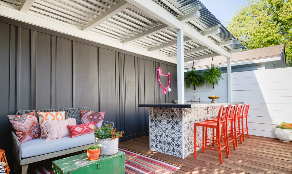 A mobile home deck with a bar and outdoor furniture