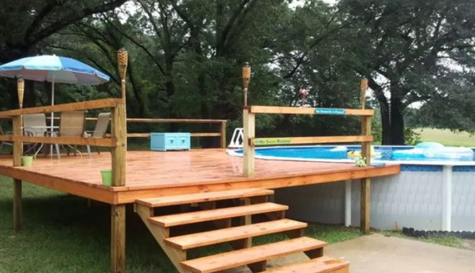 A raised deck with stairs, built around a swimming pool