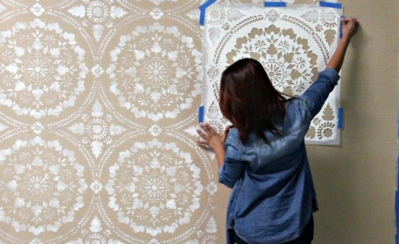 A woman doing stenciling as wallpaper
