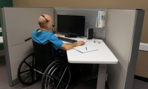 Disabled man sitting down in front of computer