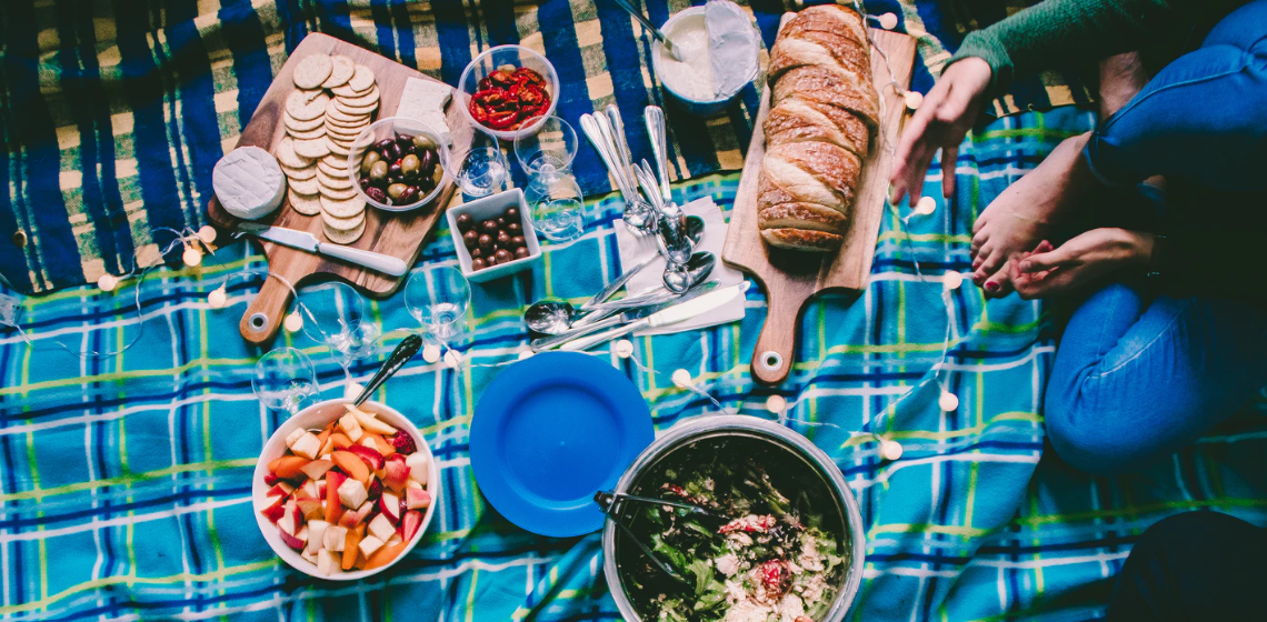 Picnic blanket with food and string lights