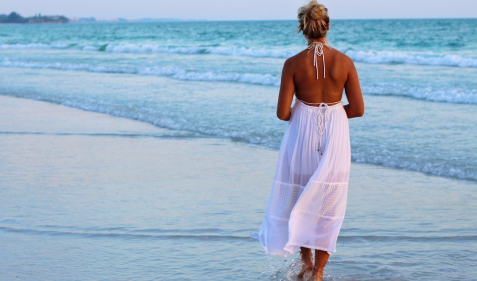 A woman wearing a backless beach dress on the beach
