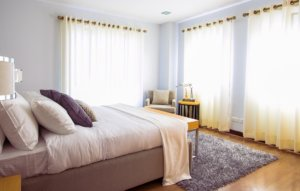 Big bedroom windows with curtains and natural lighting