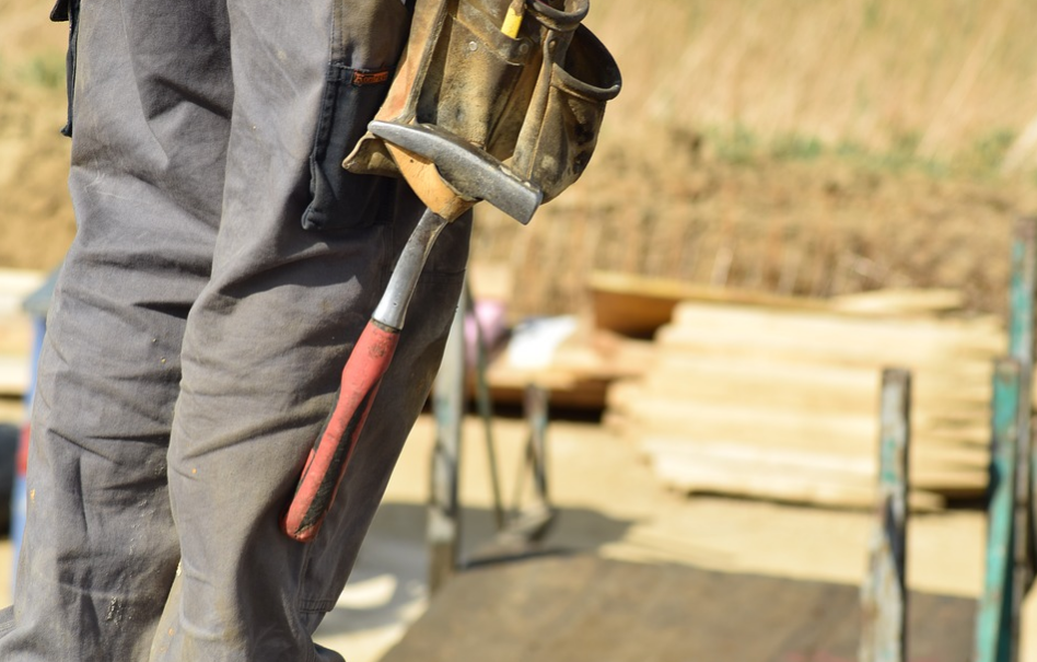 Construction worker on site holding a hammer