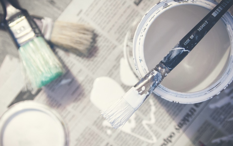Paintbrushes and a bucket of white paint