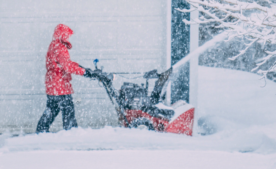 Person using snow blowing machine